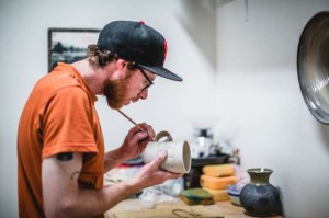 Man holding ceramic mug and applying glaze with paintbrush