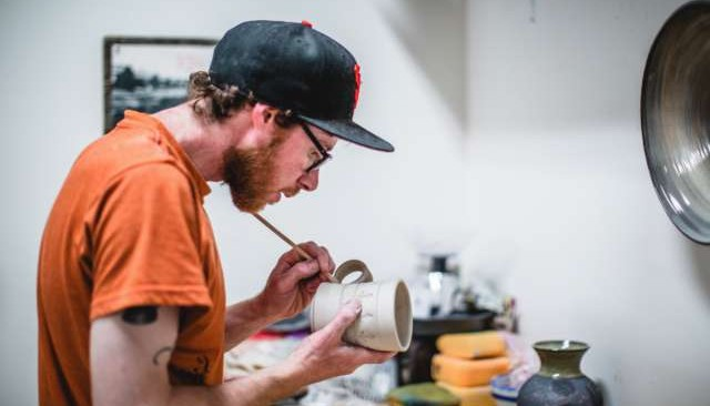 Man glazing ceramic cup with paintbrush