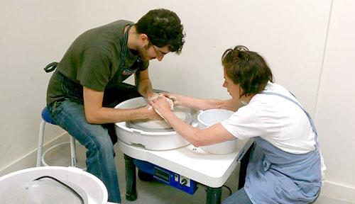 teacher helping studio on pottery wheel